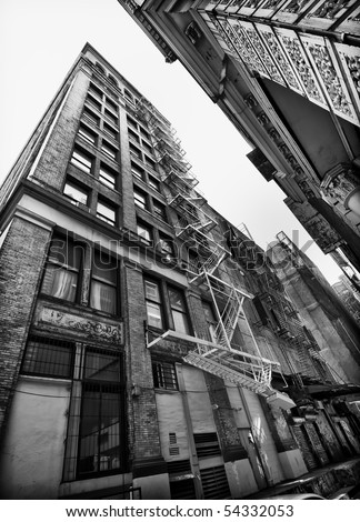 Perspective view of NYC building exterior with fire escape, Black and white. - stock photo