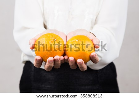 Perspective view of woman giving mandarin oranges, a tradition during Chinese New Year celebration - stock photo