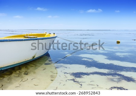 Perspective view on yellow fisher boat anchoring on african beach, low tide, shallow depth of field - stock photo