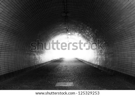 Perspective View Through a Dark Tunnel With the Light at The End - stock photo