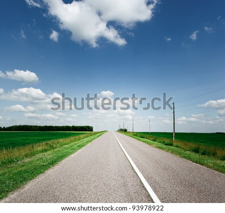 perspective view to long asphalt road over fields - stock photo