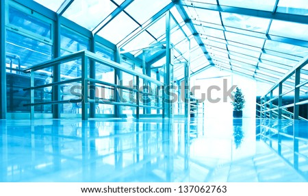perspective view to steel blue glass airport ceiling through high rise building skyscrapers, business concept of successful industrial architecture - stock photo