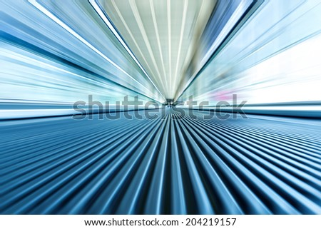 Perspective wide angle view of modern metal chrome and light blue illuminated airport, spacious high-speed technology moving escalator, fast blurred trail of steel handrail in vanishing traffic motion - stock photo