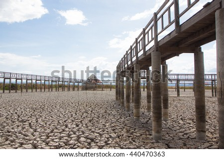 perspective wooden bridge with dry earth and cracked ground texture, broken split land with soil background - stock photo
