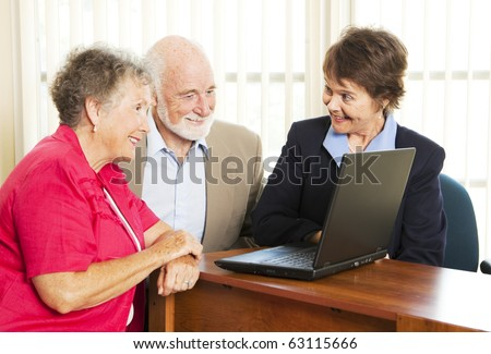 Persuasive sales woman pitches financial services to an elderly couple. - stock photo