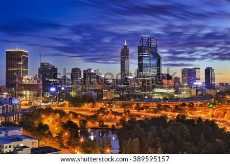 Perth city CBD at sunrise as seen from hights of Kings park. Skyscrapers of capital of Western Australia illuminated above city highways - stock photo