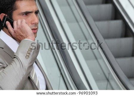 Perturbed businessman using a cellphone by an escalator - stock photo