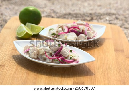 Peruvian ceviche (raw fish, red onion marinated in lime with garlic, salt, coriander) on wooden board on sand, photographed with natural light (Selective Focus, Focus on the fish piece on the top)  - stock photo
