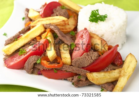 Peruvian dish called Lomo Saltado made of tomato, beef meat and onions mixed with French fries and served with rice (Selective Focus, Focus on the front) - stock photo