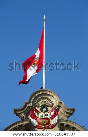 Peruvian flag waving at the top of the presidential palace with blue and clear sky, Lima, Peru - stock photo