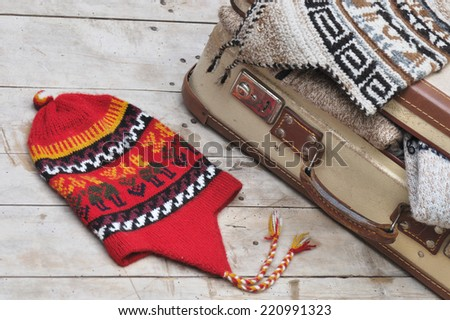peruvian hat on wooden board with old  suitcase full of warm clothes - stock photo
