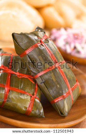 Peruvian tamales (traditional Sunday breakfast) wrapped in banana leaves, in which they are cooked. Inside is a corn-based dough with meat (Selective Focus, Focus on the front of the standing tamale) - stock photo