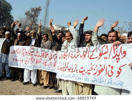 PESHAWAR, PAKISTAN - JAN 11: Supporters of WAPDA Hydro Union chant slogans in favor of their demands during a protest demonstration at Peshawar press club on January 11, 2011in Peshawar. - stock photo