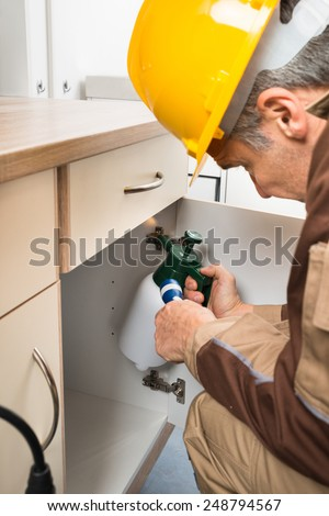 Pest Control Worker In Workwear With Flashlight And Spraying Pesticides Inside Cabinet - stock photo