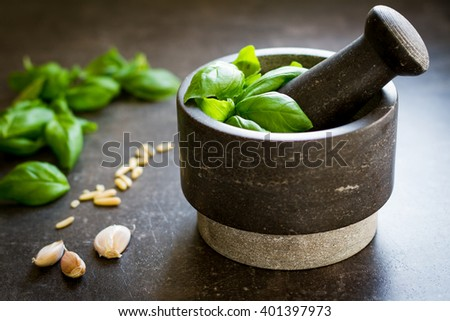 Pesto from basil, pine seeds and garlic preparing in stony mortar - stock photo