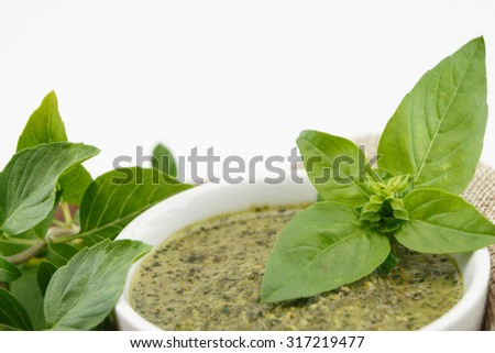 Pesto sauce and basil leaves, isolated on white background - stock photo