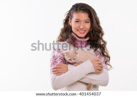Pet and smiling girl. Chinese appearance of a teenager. Ginger cat in hugs. Happy pet. Cute animal for girls. White background. Studio photo shoot. Cool wallpaper. - stock photo