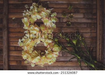 petals flowers form March  8  frame Women's Day postcard on brown wood board  background in rustic style for - stock photo