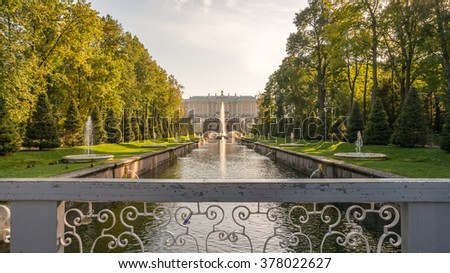 Peterhof (Petrodvorets) The Great Cascade Samson Rending open Jaws of the Lion. Peterhof Fountains and Gardens from Out of Focus Bridge over canal under Dramatic Golden Sky Sunset in Summer, Russia - stock photo