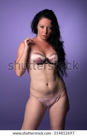 Petite pretty Italian brunette in pink lingerie - stock photo