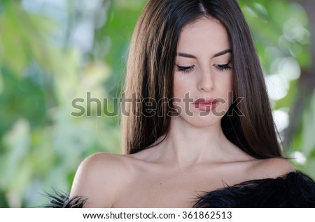 Petite young woman with very long hair wear only her lamb fur vest, pose against blur greens background - stock photo