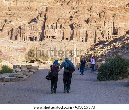 PETRA, JORDAN - OCTOBER 28, 2014: Unidentified locals and tourists on colonnaded street with urn, silk and royal tombs on background. - stock photo