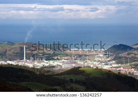 Petrochemical refinery with smoke polluting environment - stock photo