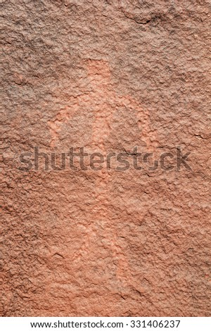 petroglyph of a man on a varnished red sandstone rock - stock photo