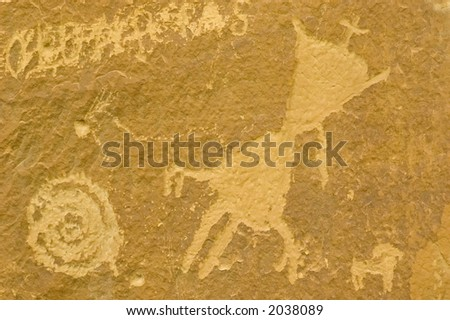 petroglyph of humanoid figure with spiral and animal in chaco canyon new mexico - stock photo