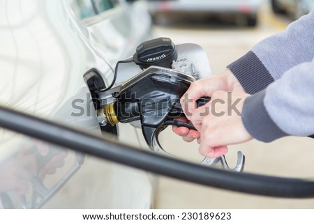 Petrol or gasoline being pumped into a motor vehicle car. Closeup of man pumping gasoline fuel in car at gas station. - stock photo