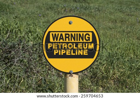 Petroleum pipeline warning sign in green grassy meadow.   - stock photo