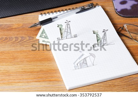 Petroleum pumpjack and oil rigs. Concept from paper on the table. - stock photo