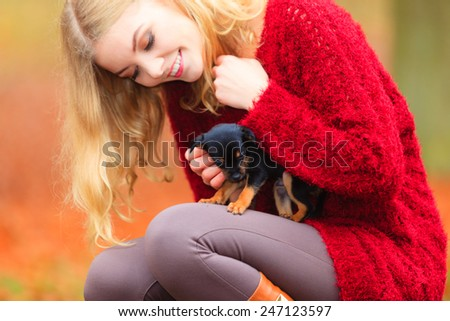 Pets and people, pet adoption. Woman playing with her little dog pet outdoor, hugging lovingly embraces her puppy. - stock photo