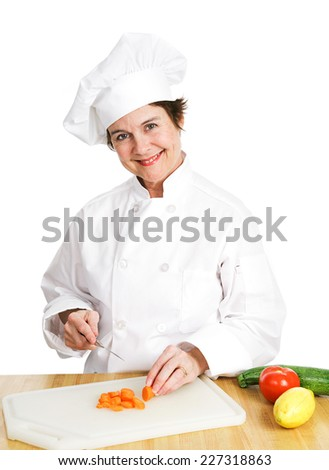Petty female chef in her uniform, cutting up a variety of fresh organic vegetables on her cutting board in the kitchen.  Isolated on white background.   - stock photo