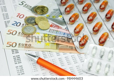 Pharma medicine pills and drugs with money and pen - stock photo
