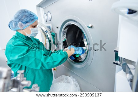 pharmaceutical factory woman worker operating tablet glazing production line at pharmacy industry manufacture factory - stock photo