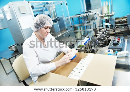 pharmaceutical factory worker at pharmacy industry manufacture packing medicine into boxes - stock photo