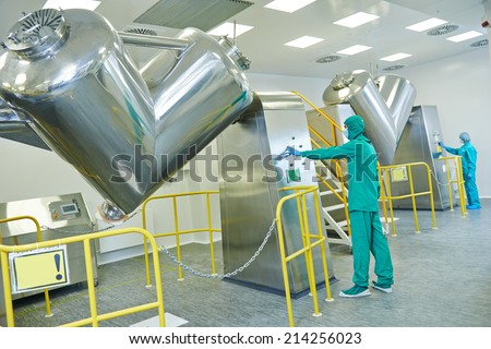 pharmaceutical factory workers operating powder mixer machine on production line in pharmacy industry manufacture factory - stock photo