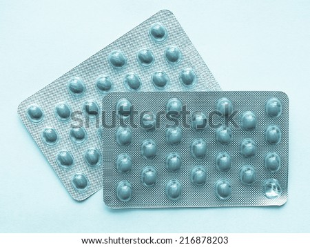 Pharmaceutical over the counter or prescription pills - cool cyanotype - stock photo