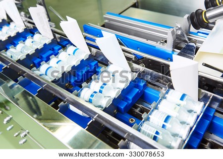 pharmaceutical packing production line conveyor at manufacture pharmacy factory - stock photo
