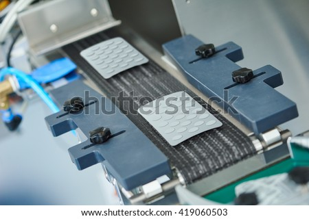 pharmaceutical tablet pill production conveyer - stock photo