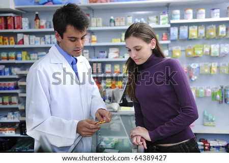 Pharmacist advising client at pharmacy how to take medicine - stock photo