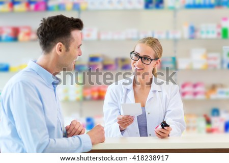 Pharmacist and client at pharmacy  - stock photo
