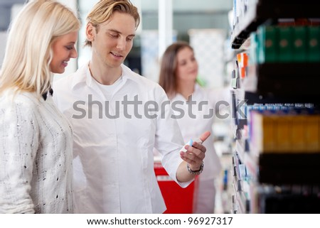 Pharmacist And Customers At Pharmacy In Front Of Shelves With Pharmaceuticals. - stock photo