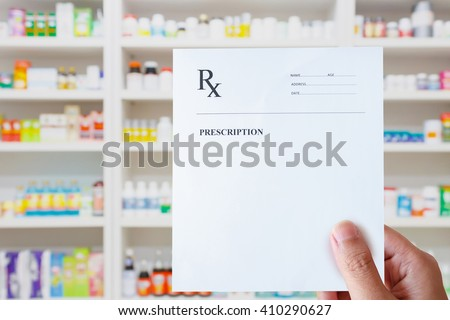 pharmacist hand holding prescription rx paper in hand over pharmacy store background - stock photo