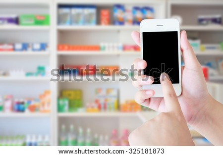pharmacist hand holding smart phone with blur some shelves of drug in the pharmacy drugstore - stock photo
