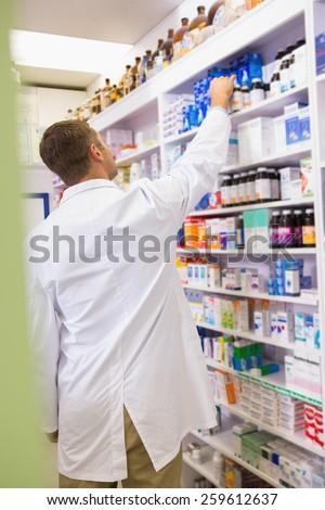 Pharmacist in lab coat taking jar from shelf in the pharmacy - stock photo