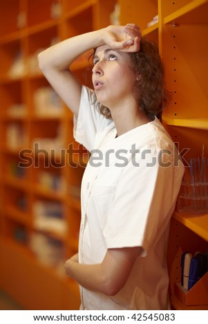 Pharmacist leaning at shelf and taking a rest - stock photo