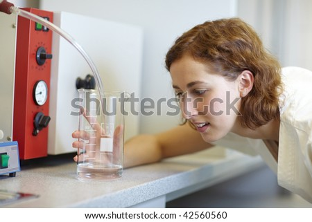 Pharmacist looking at measuring cup in laboratory - stock photo