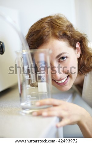 Pharmacist looking through measuring cup in laboratory - stock photo